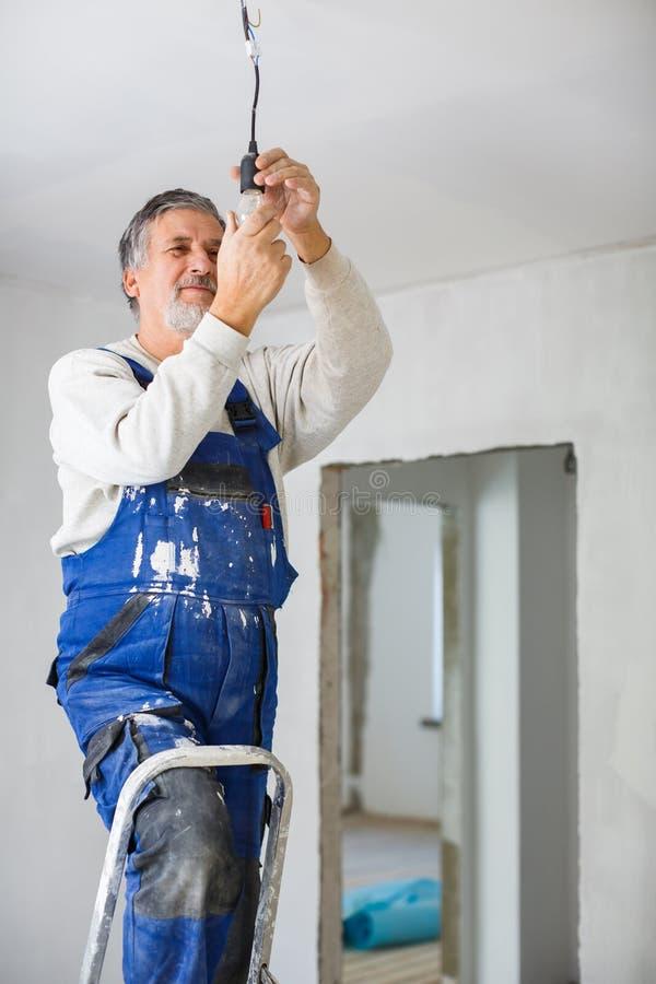 Uomo senior che installa una lampadina in un appartamento di recente rinnovato i immagine stock