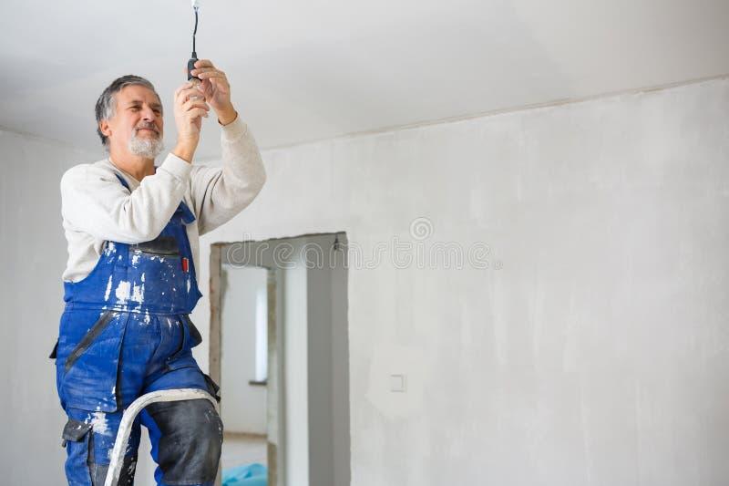 Uomo senior che installa una lampadina in un appartamento di recente rinnovato i fotografie stock