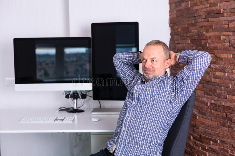 Uomo senior che lavora nell'ufficio fotografia stock
