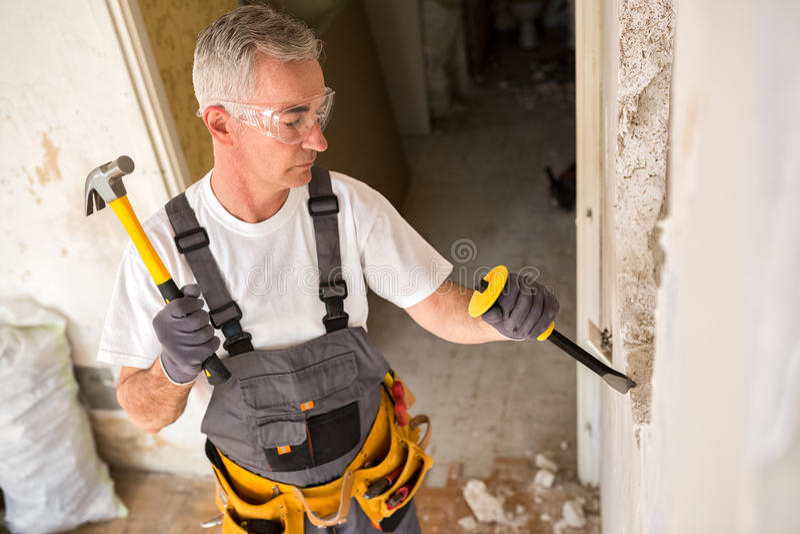 Uomo senior che lavorano con il martello e strumento mentre demolisca la parete fotografia stock libera da diritti