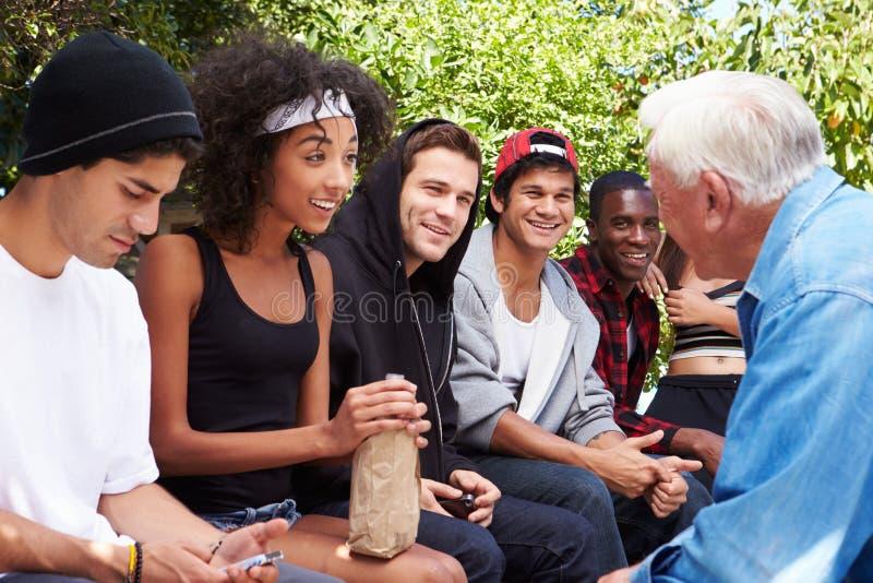 Uomo senior che parla con il gruppo dei giovani fotografia stock