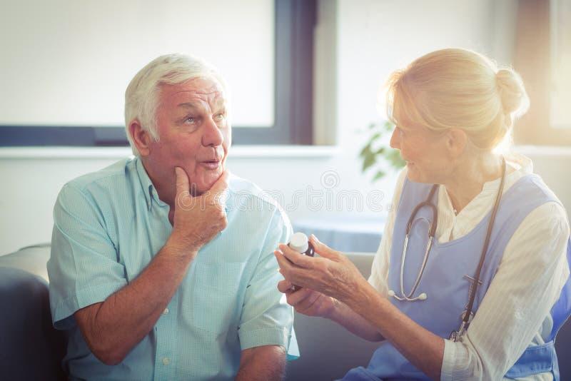 Uomo senior che parla con medico femminile fotografie stock