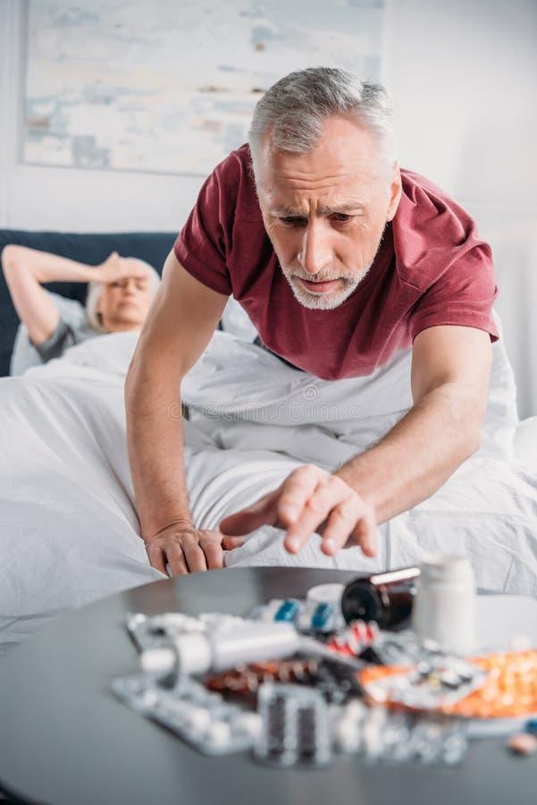 Uomo senior che prende le medicine dalla tavola in camera da letto immagini stock