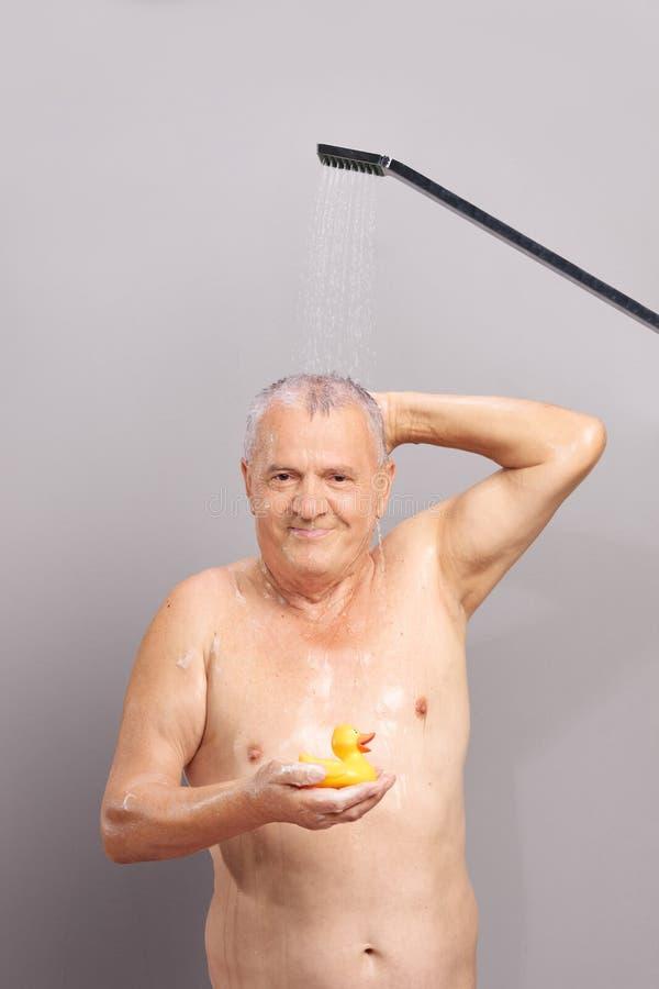 Uomo senior che prende una doccia e che tiene anatra di gomma immagini stock libere da diritti