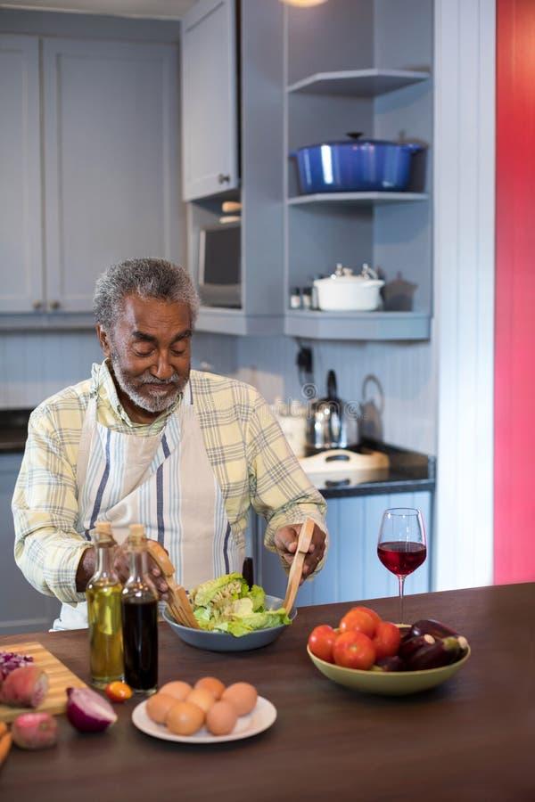 Uomo senior che produce insalata mentre sedendosi nella cucina immagini stock libere da diritti