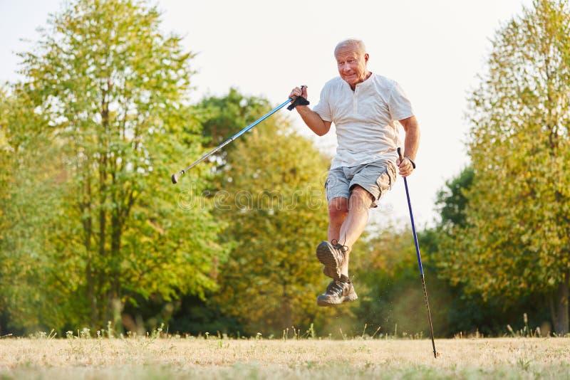 Uomo senior che salta durante il suo giro d'escursione fotografie stock