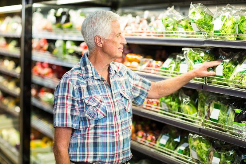 Uomo senior che seleziona insalata fotografie stock
