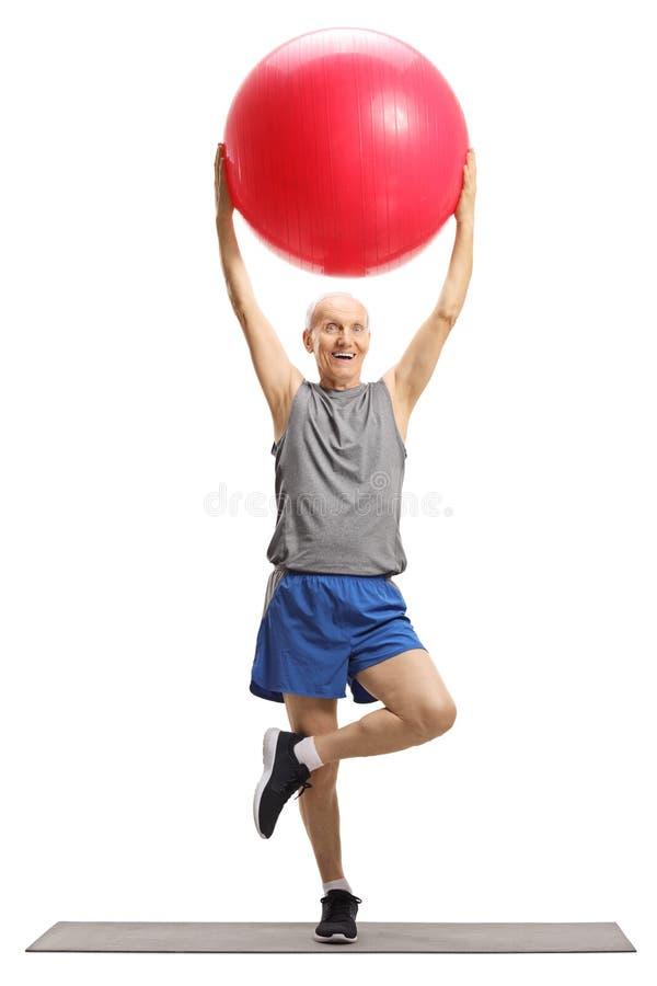 Uomo senior che si esercita con una palla di forma fisica e che allunga una gamba fotografia stock libera da diritti