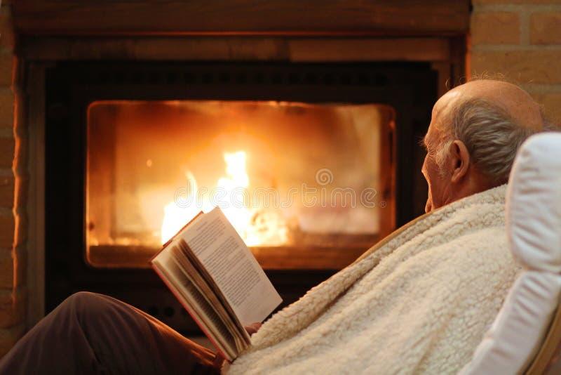 Uomo senior che si rilassa dal camino fotografie stock libere da diritti