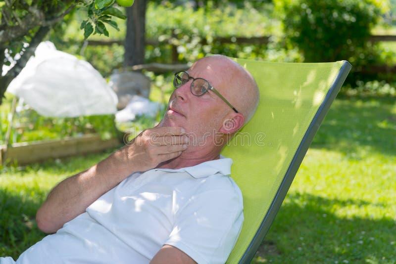 Uomo senior che si rilassa nella sedia a sdraio nel suo giardino fotografie stock libere da diritti