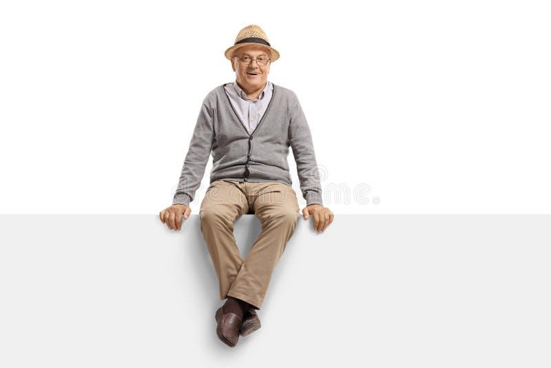 Uomo senior che si siede su un segno in bianco del tabellone per le affissioni fotografia stock