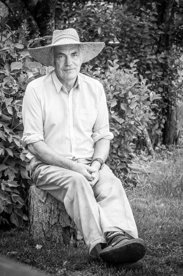 Uomo senior che si siede su una connessione la sua iarda di aria aperta fotografia stock libera da diritti