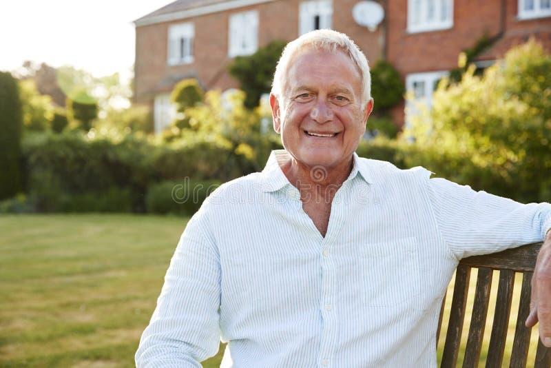 Uomo senior che si siede sul banco del giardino alla luce solare di sera fotografie stock libere da diritti