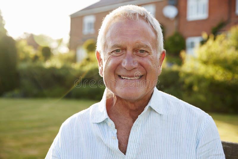 Uomo senior che si siede sul banco del giardino alla luce solare di sera fotografia stock libera da diritti
