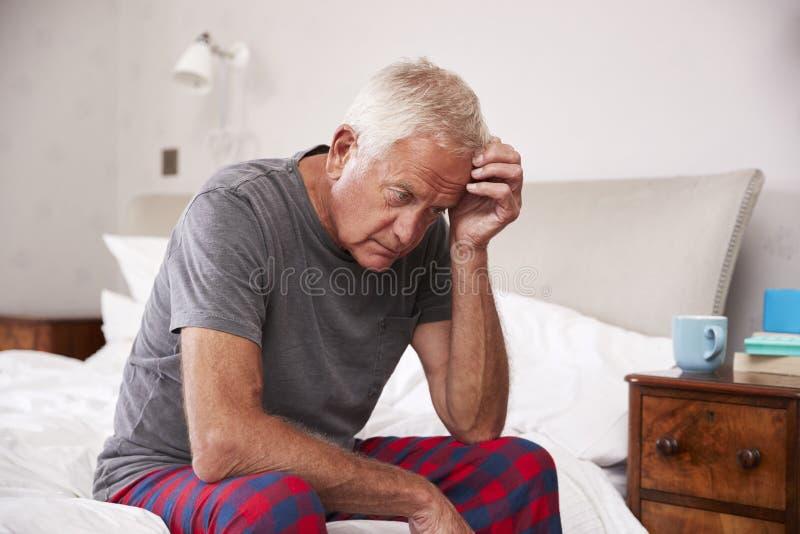 Uomo senior che si siede sul letto a casa che soffre dalla depressione fotografia stock
