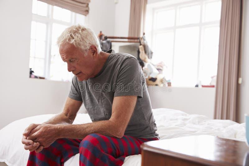 Uomo senior che si siede sul letto a casa che soffre dalla depressione fotografie stock