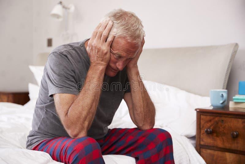 Uomo senior che si siede sul letto a casa che soffre dalla depressione fotografie stock libere da diritti