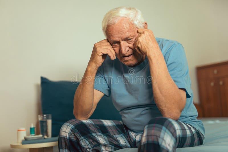 Uomo senior che si siede sul letto che soffre dalla depressione fotografia stock libera da diritti