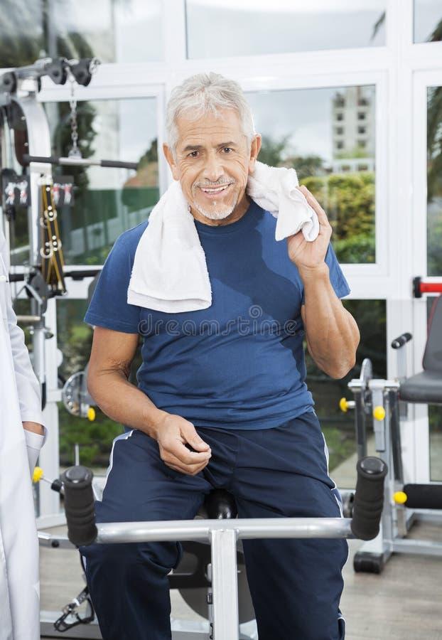 Uomo senior che si siede sulla bici di esercizio al centro di forma fisica di riabilitazione immagine stock libera da diritti