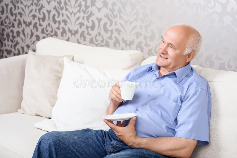 Download Uomo Senior Che Si Siede Sullo Strato Con La Tazza Fotografia Stock - Immagine di bevanda, cheerful: 55351220