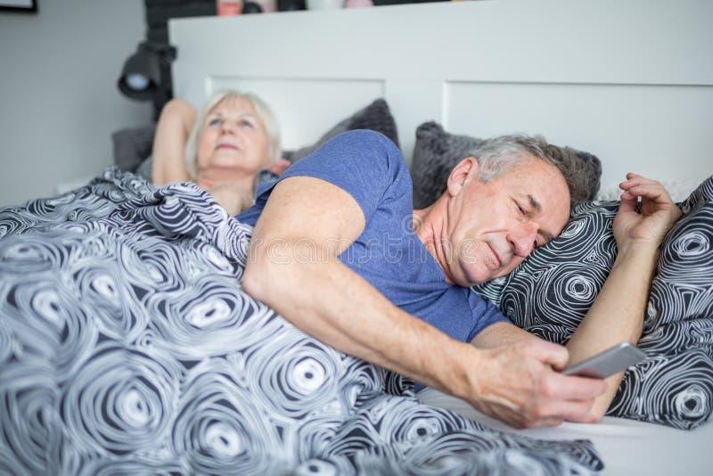 Uomo senior che si trova a letto facendo uso dello smartphone fotografia stock libera da diritti