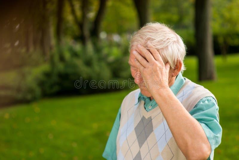 Uomo senior che tocca la sua fronte fotografia stock libera da diritti