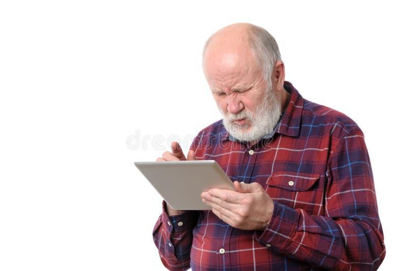 Uomo senior che tocca qualcosa allo schermo di computer della compressa, isolato su bianco immagine stock libera da diritti