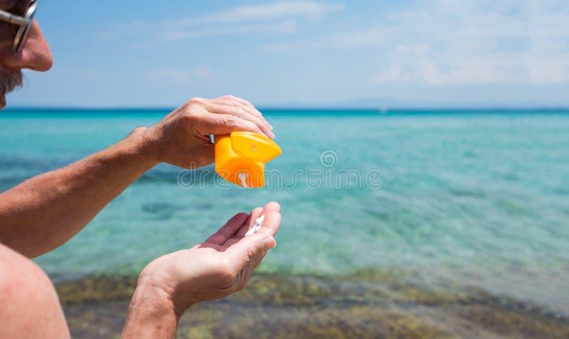 Uomo senior che usando protezione del sole sulle vacanze estive immagini stock libere da diritti