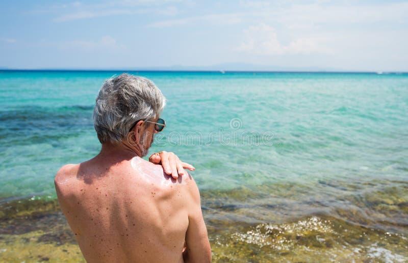 Uomo senior che usando protezione del sole sulle vacanze estive immagini stock