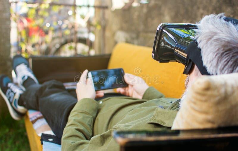 Uomo senior che usando realtà virtuale su un letto di sofà immagine stock libera da diritti
