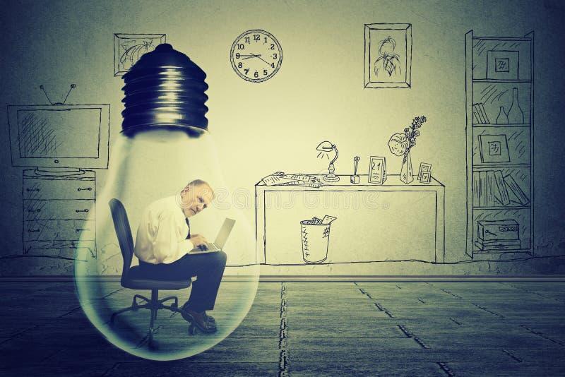 Uomo senior che utilizza lavorare al computer che si siede dentro la lampada elettrica nell'ufficio corporativo fotografia stock