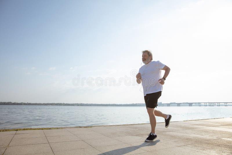 Uomo senior come il corridore con il bracciale o inseguitore di forma fisica alla riva del fiume fotografia stock libera da diritti