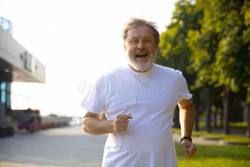 Uomo senior come il corridore con il bracciale o inseguitore di forma fisica alla via della città fotografie stock