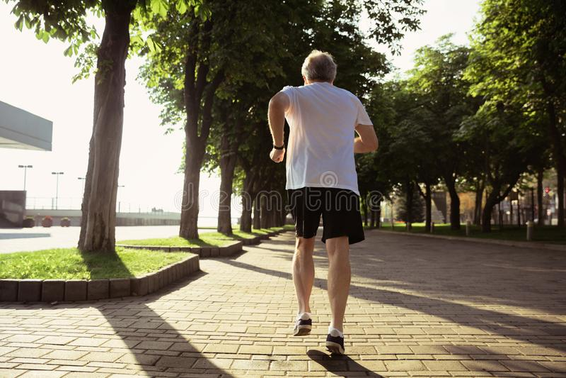 Uomo senior come il corridore con il bracciale o inseguitore di forma fisica alla via della città fotografie stock libere da diritti