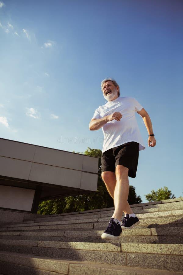 Uomo senior come il corridore con il bracciale o inseguitore di forma fisica alla via della città immagini stock