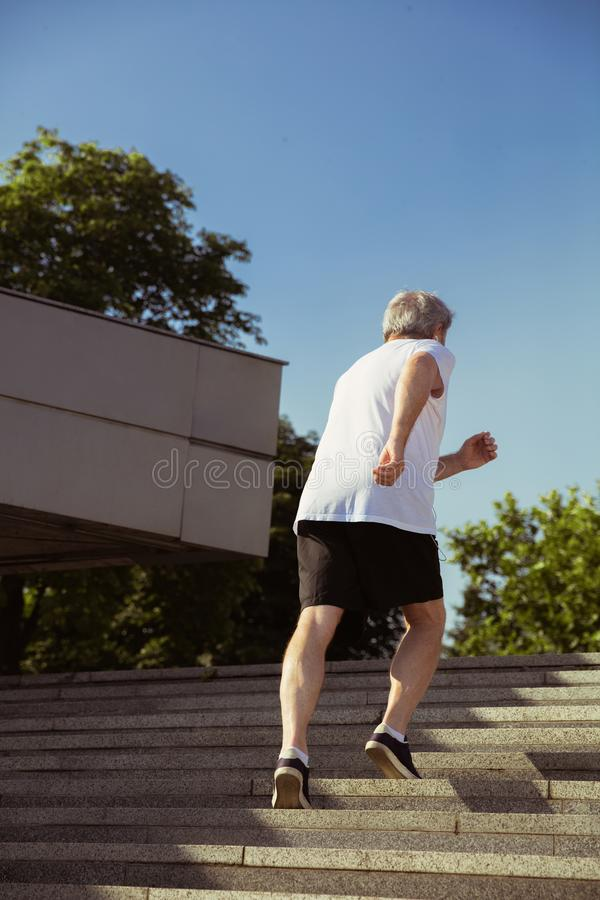 Uomo senior come il corridore con il bracciale o inseguitore di forma fisica alla via della città immagine stock