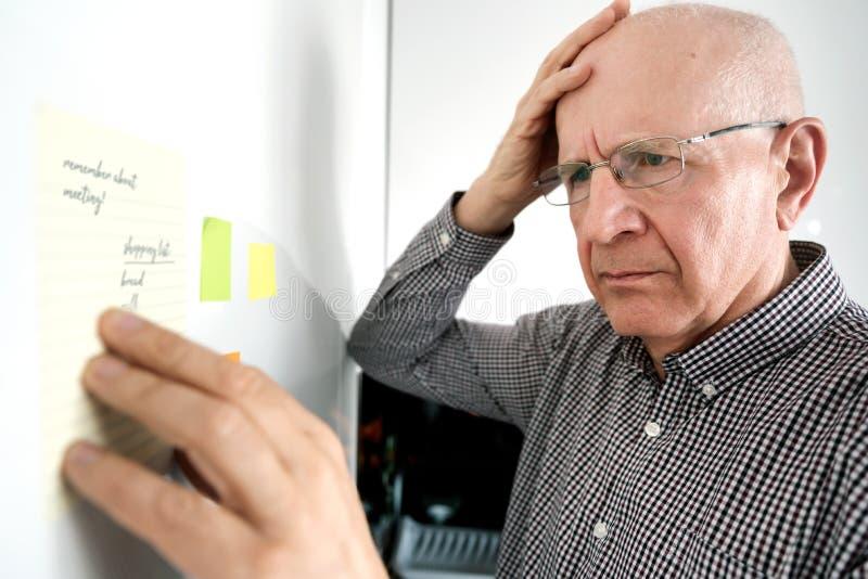 Uomo senior con demenza, esaminante le note fotografie stock