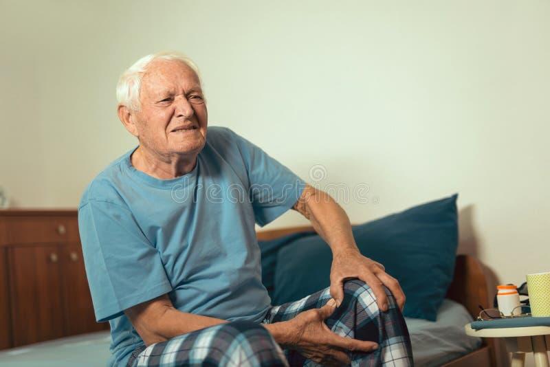 Uomo senior con dolore di osteoartrite nel ginocchio fotografie stock libere da diritti