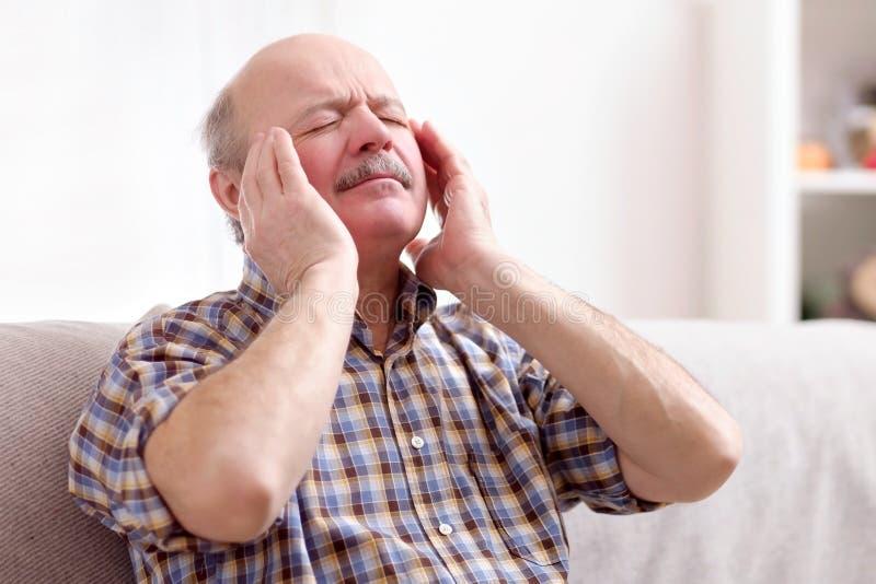 Uomo senior con i baffi che hanno un'emicrania a casa fotografie stock
