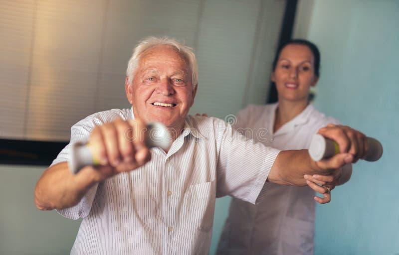 Uomo senior con i dumbbells nella riabilitazione immagini stock
