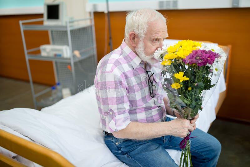 Uomo senior con i fiori in ospedale fotografia stock