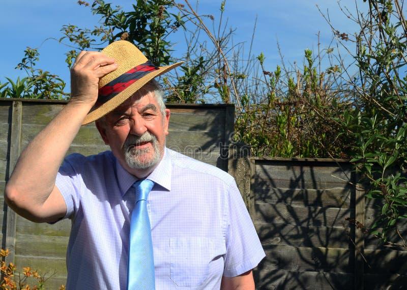 Uomo senior con il cappello di paglia che dice buon giorno fotografie stock