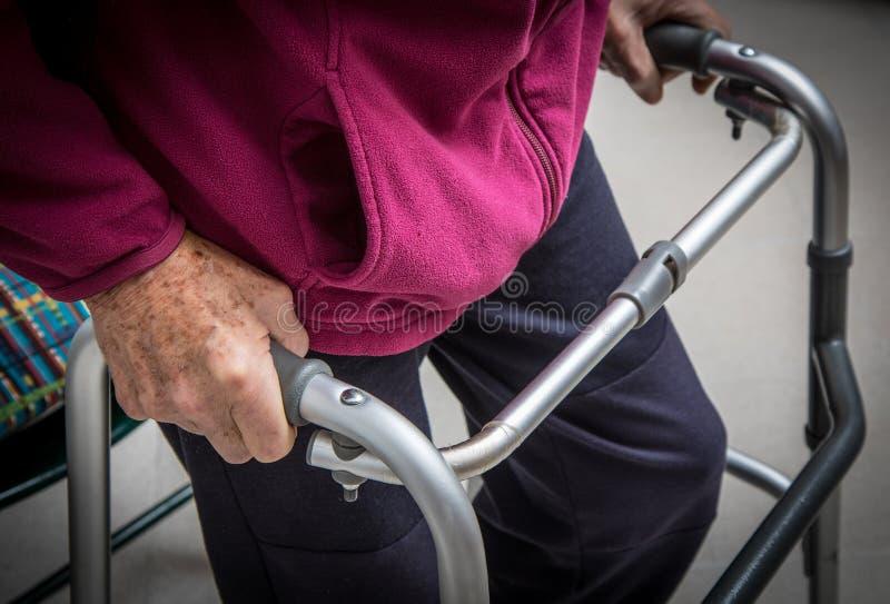 Uomo senior con il recupero di inabilità a casa che cammina il primo piano delle strutture immagini stock