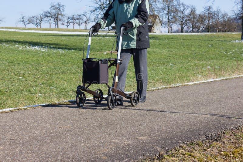 uomo senior con il rollator una pista ciclabile e un giorno di inverno soleggiato fotografia stock