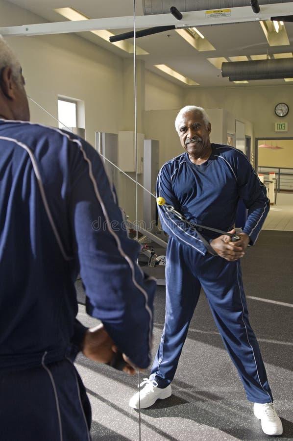 Uomo senior con la banda di allungamento di esercizio immagini stock