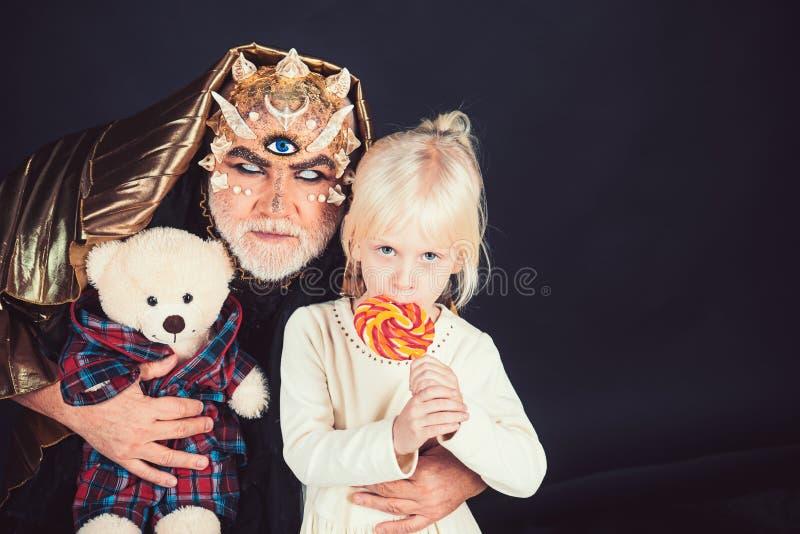 Uomo senior con la barba bianca vestita come il mostro che racconta storia alla bambina Concetto di favola Uomo con le spine o immagine stock