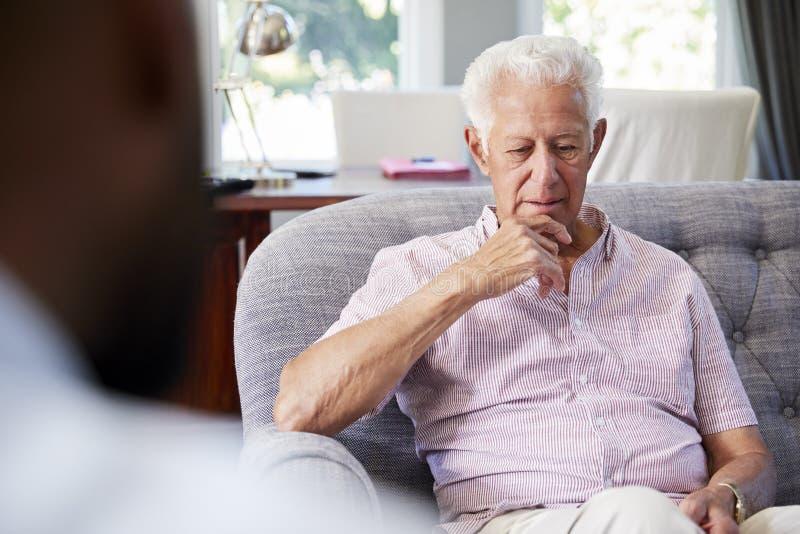 Uomo senior con la depressione che ha terapia con lo psicologo immagine stock