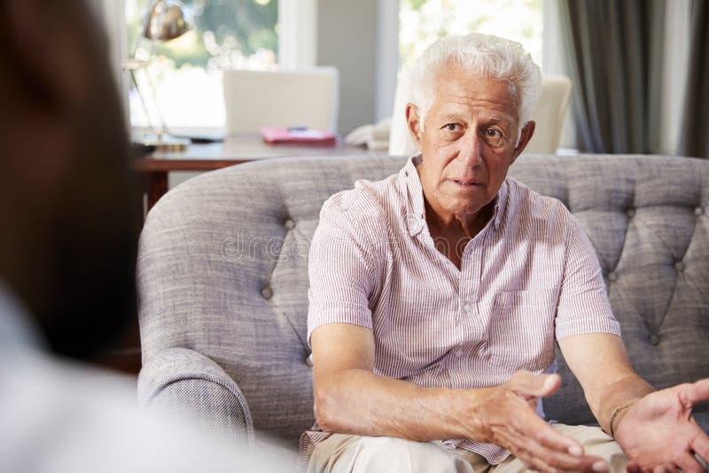 Uomo senior con la depressione che ha terapia con lo psicologo immagini stock libere da diritti