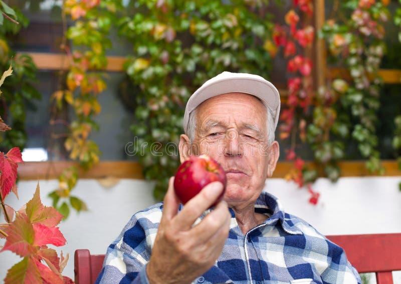 Uomo senior con la mela fotografia stock