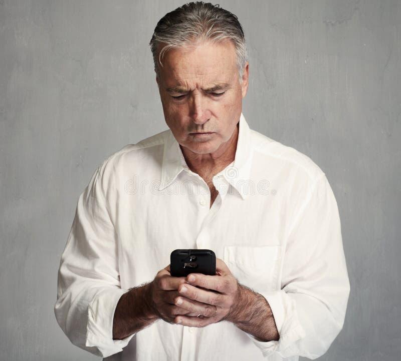 Uomo senior con lo smartphone fotografie stock